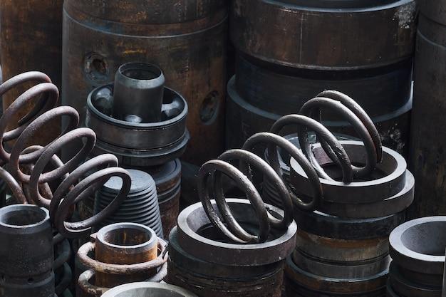 Des pièces de quincaillerie rouillées de turboperceuses de différents diamètres sont sur le sol dans un atelier semi-sombre