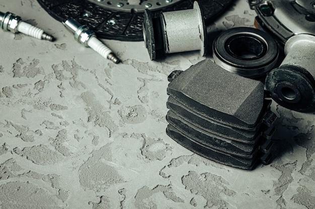 Pièces de voiture sur fond de béton texturé gris, espace copie