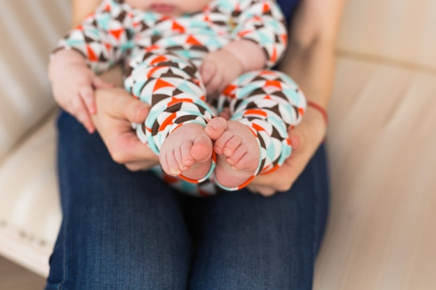 Pied de bébé dans les mains des femmes, gros plan. jolie petite jambe d'enfant. maternité, amour, soins, nouveau concept de vie.