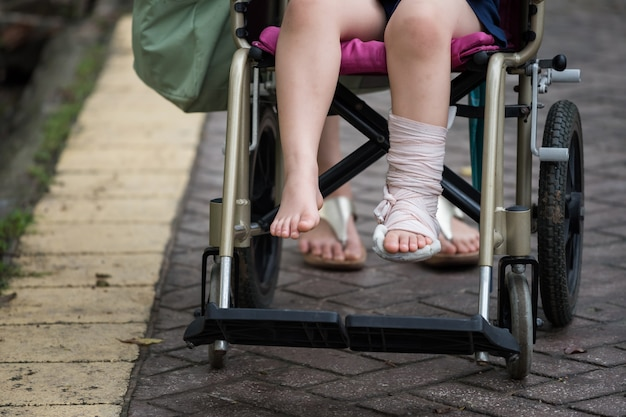 Pied cassé d'un enfant en fauteuil roulant dans le parc