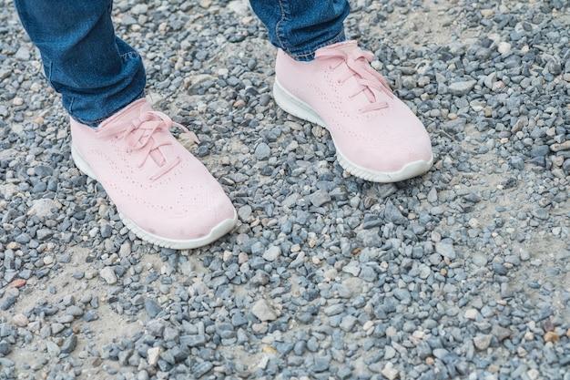Pied de femme gros plan avec chaussure rose debout seul sur fond texturé de sol