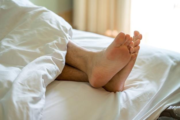 Pied homme être fatigué sur le lit, histoire de lit couple