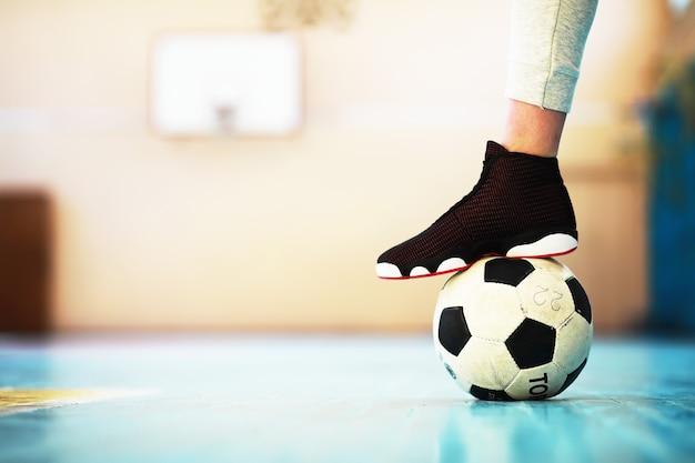 Un Pied Humain Repose Sur Le Football Sur Sol En Béton. Photo D'un Ballon De Football Et De Baskets Dans Un Plancher En Bois. Photo Premium