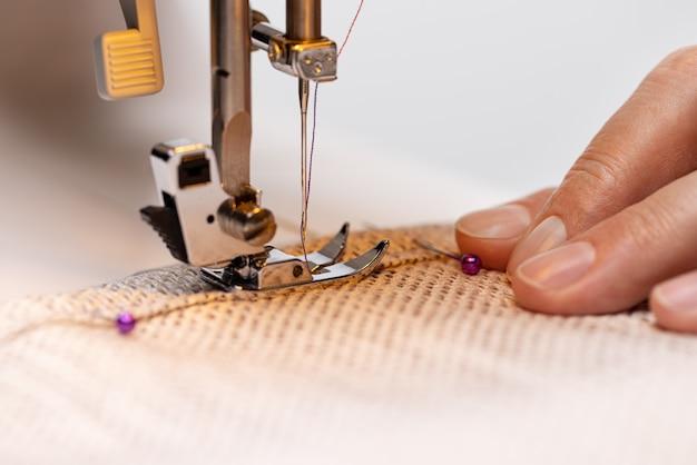 Pied de machine à coudre sur tissu avec aiguille et fil prêt à coudre la main des opérateurs sur le mater