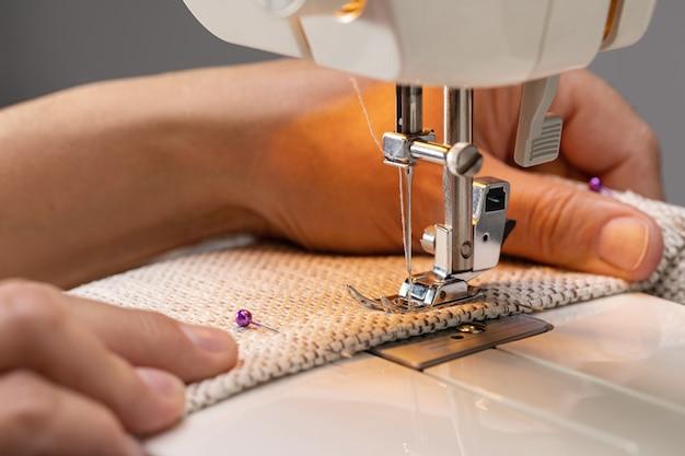 Pied de machine à coudre sur tissu avec aiguille et fil prêt à coudre la main des opérateurs sur le materi