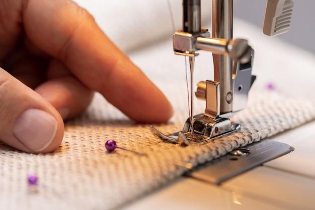 Pied de machine à coudre sur tissu avec aiguille et fil prêt à travailler main d'opérateur sur le matériel