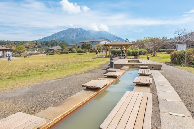 Pied onsen avec fond de ciel bleu, montagne et mer sakurajima, kagoshima, kyushu, japon