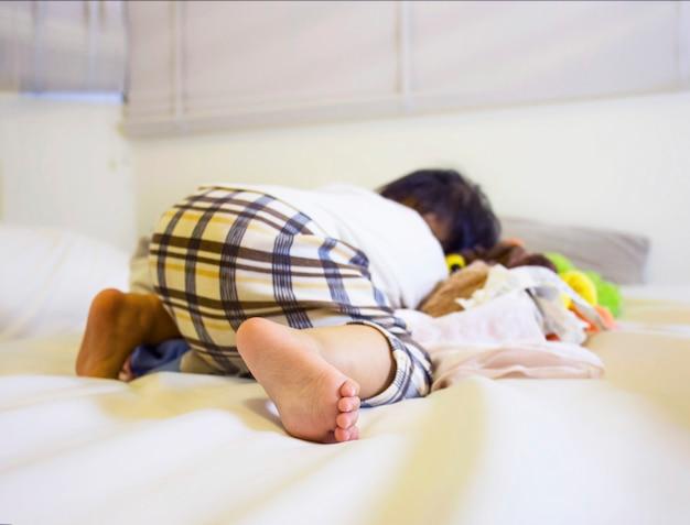 Pied de la petite fille mignonne endormie jouant dans la chambre blanche avec son ours en peluche