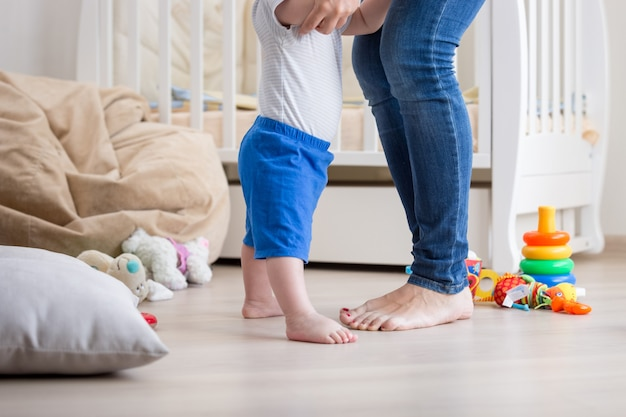 Pieds adorables de bébé et de mère sur le sol au salon