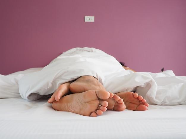 Pieds des amoureux de couple ayant des rapports sexuels sur un lit le matin avec la luxure et l'amour