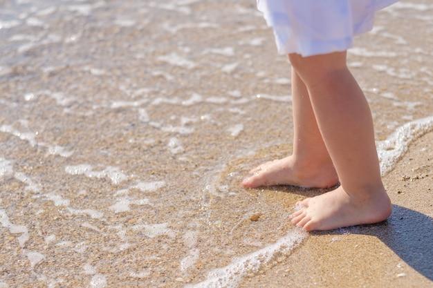 Pieds de bébé aux pieds nus se bouchent sur le sable de la plage de la mer