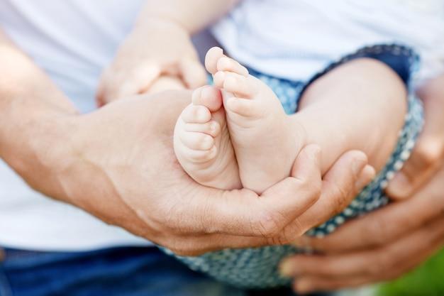 Pieds de bébé dans les mains du père. pieds d'enfants minuscules sur les mains mâles agrandi en plein air. papa et son enfant. concept de famille heureuse. belle image conceptuelle de la parentalité.
