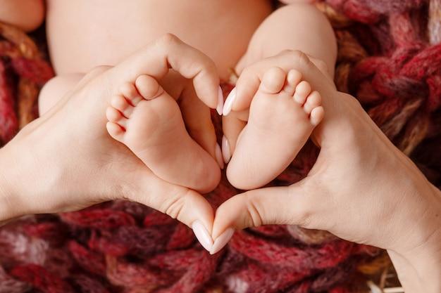 Pieds de bébé dans les mains de la mère - gros plan en forme de foyer.