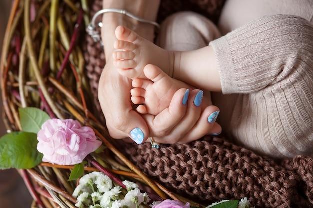Pieds de bébé dans les mains de la mère. pieds de petit bébé nouveau-né sur les mains en forme de femme gros plan. maman et son enfant. concept de famille heureuse. belle image conceptuelle de la maternité
