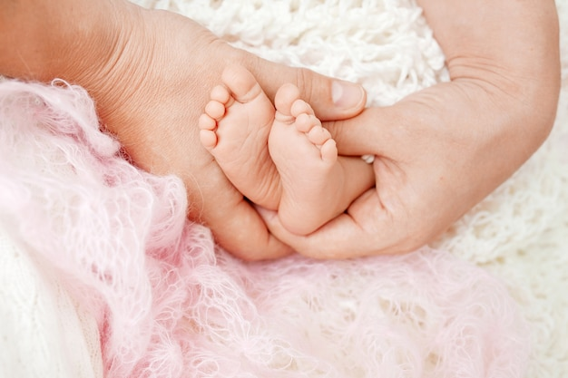 Pieds de bébé dans les mains de la mère.