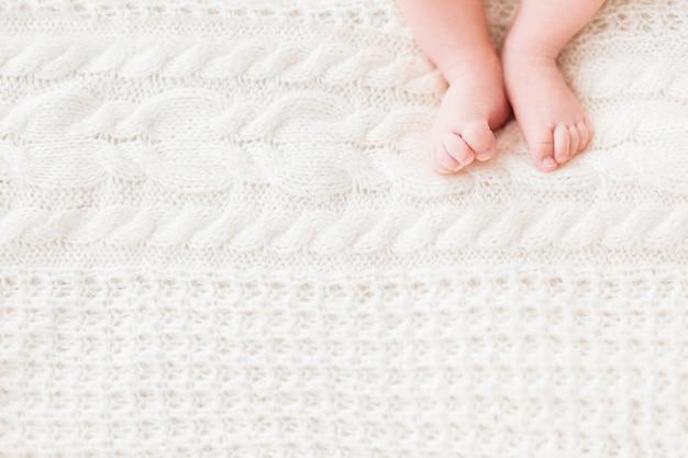 Pieds de bébé sur fond tricoté blanc.
