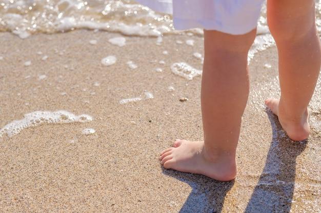 Pieds de bébé gros plan sur le sable de la plage de la mer l'eau de mer lave les pieds enfance heureuse reste à la mer journée ensoleillée d'été copie espace