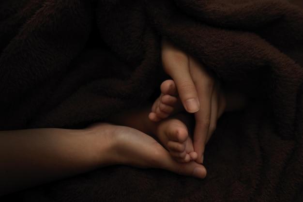 Pieds de bébé nouveau-né dans les mains de la mère, fond sombre