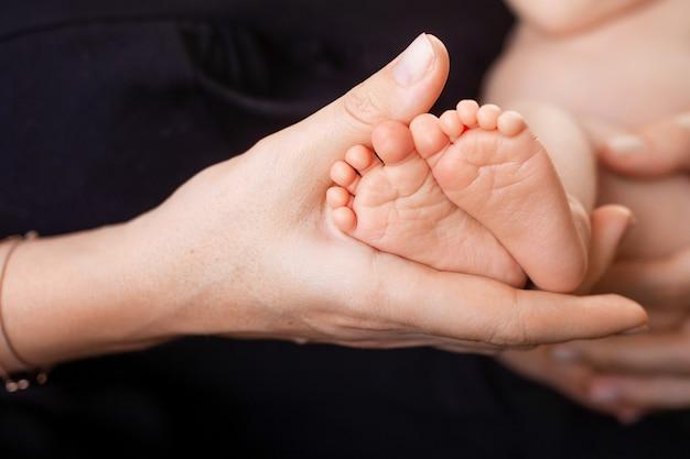 Pieds de bébé nouveau-né dans les mains de la mère sur la scène noire. maman tenant son enfant.