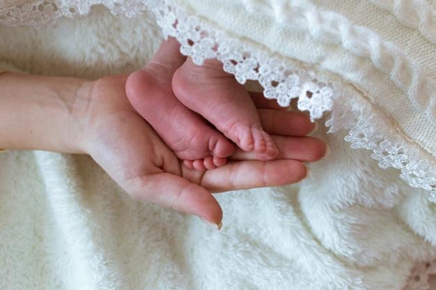 Pieds de bébé en vêtements blancs