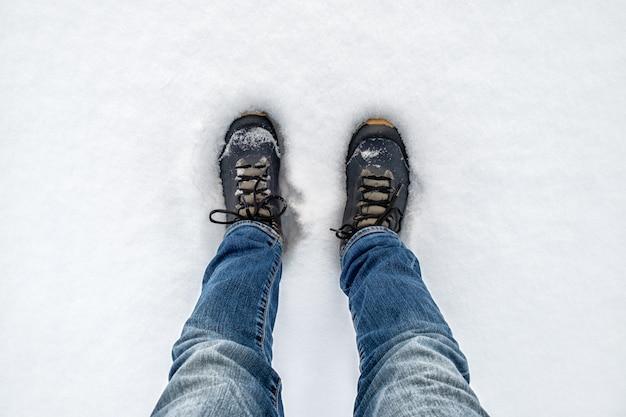 Pieds en bottes de trekking noires sur la neige