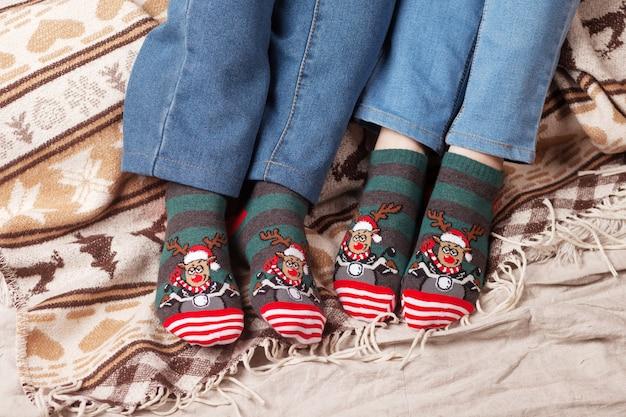 Pieds en chaussettes de noël sur plaid de noël. couple assis sur la couverture, se détend en se réchauffant les pieds dans des chaussettes en laine. vacances d'hiver et de noël concep