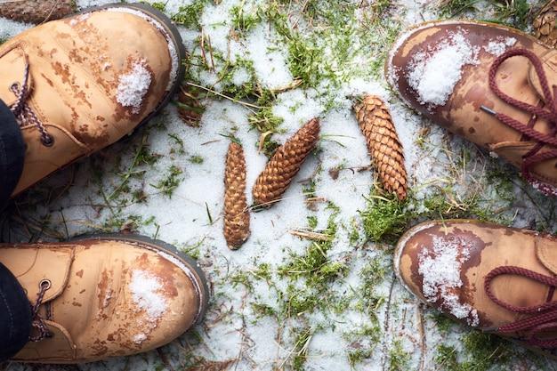 Pieds de couple en bottes de voyage sur un sol enneigé moussu dans la forêt d'hiver. concept de voyage.