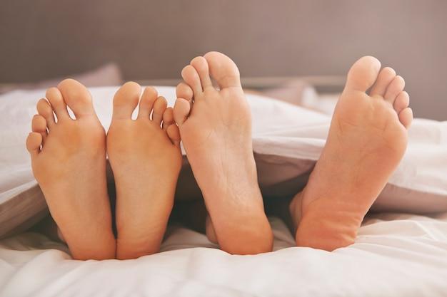 Pieds de couple dans un lit confortable