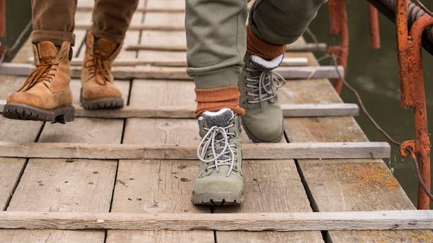 Pieds de couple gros plan sur pont en bois
