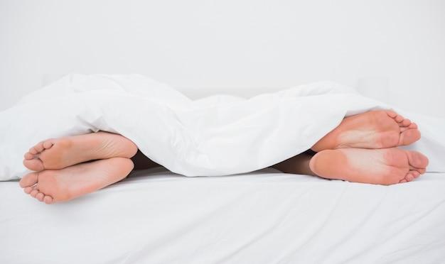 Pieds d'un couple sur leurs côtés opposés au lit