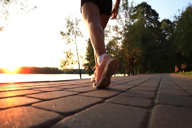 Pieds de coureur courant sur la route en gros plan sur la chaussure, en plein air au coucher du soleil ou au lever du soleil.