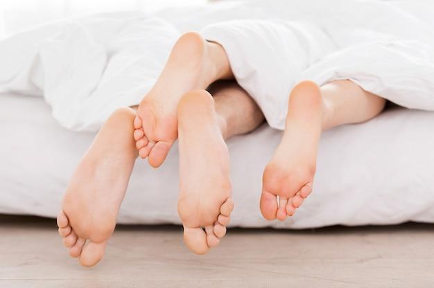 Pieds de la couverture. gros plan des pieds féminins et masculins s'étendant de la couverture