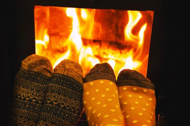 Pieds dans des chaussettes en laine d'amoureux de couple se réchauffant par un feu douillet