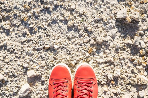Pieds dans des chaussures roses décontractées sur le fond de pierre.