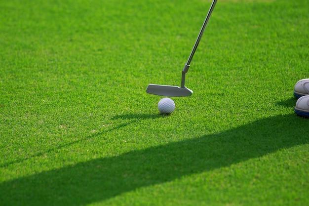 Pieds du joueur de golf féminin mettant au vert.