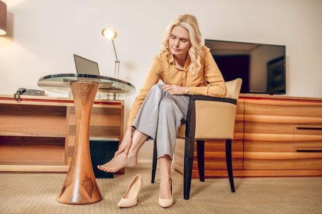 Pieds endoloris. femme blonde à la fatigue et enlevant les chaussures