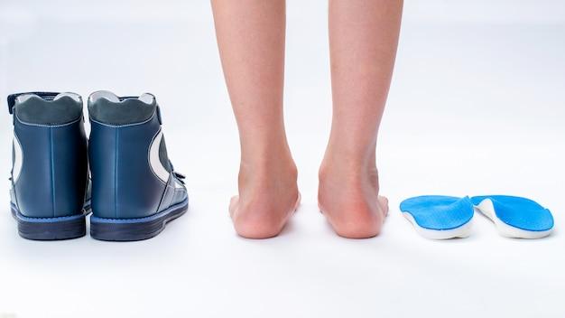 Pieds de l'enfant avec des chaussures orthopédiques insolées
