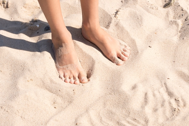 Les pieds de l'enfant dans le sable
