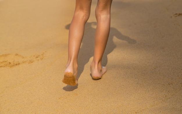 Pieds d'un enfant qui longe la plage.