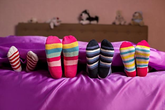 Pieds d'enfants dans des chaussettes colorées. chaussettes lumineuses colorées pour enfants. ils pensent qu'ils sont cachés. cache-cache.
