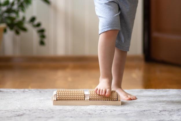 Pieds d'enfants sur un masseur à rouleaux en bois