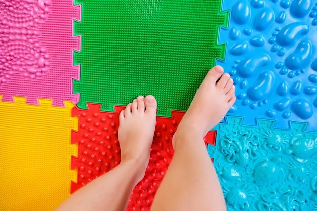 Pieds d'enfants sur tapis orthopédiques, prévention des pieds plats.
