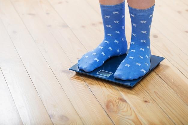 Pieds féminins en chaussettes sur la balance au sol