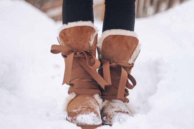 Pieds féminins dans des bottes chaudes en hiver sur le sol enneigé gros plan