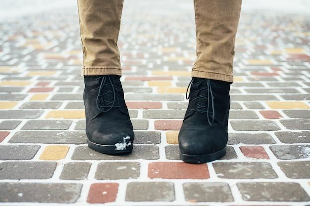Pieds féminins dans une élégante bottes d'hiver noires debout sur un trottoir enneigé en hiver, gros plan