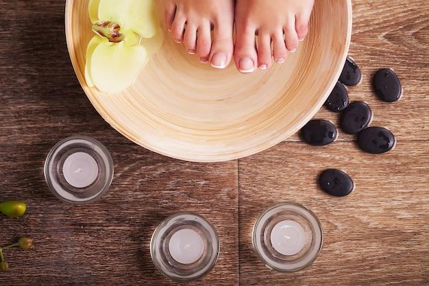 Pieds féminins avec des gouttes d'eau, bols de spa, serviettes, fleurs et bougies.