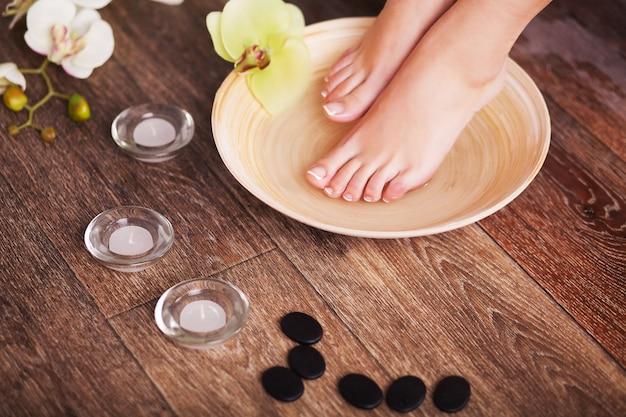 Pieds féminins manucurés dans un bol en bois spa avec des fleurs et de l'eau closeup