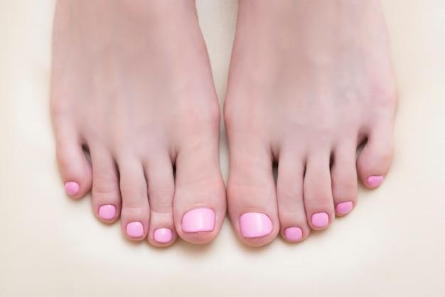 Pieds féminins avec une pédicure rose