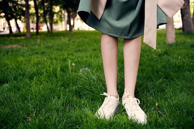 Pieds féminins sur la pelouse à pied dans le parc à l'extérieur