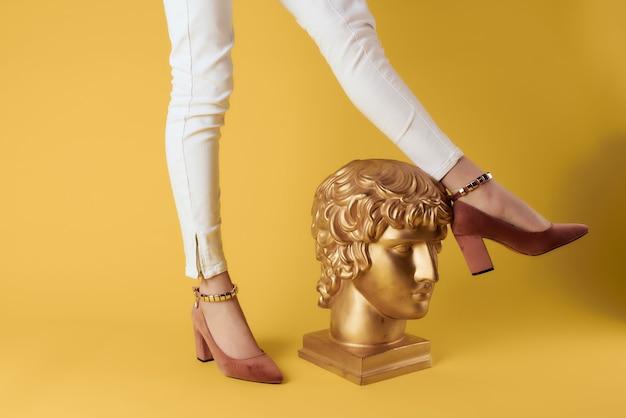 Pieds féminins tête de plâtre posant la mode des chaussures